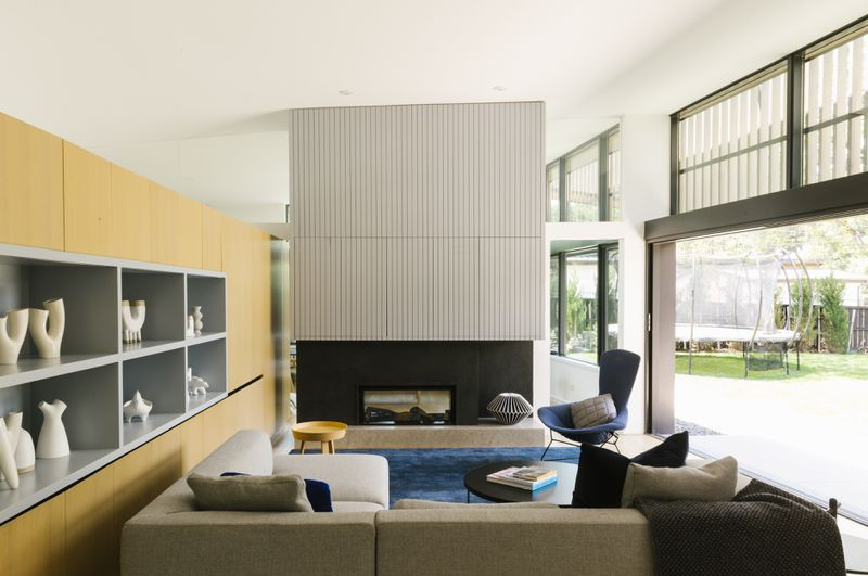 An open living room features a beige sectional sofa facing a modern gray fireplace. A blonde wood wall of cabinetry stands on the left, where gray shelves hold white sculptural objects. A large opening leads to the outside on the right side.
