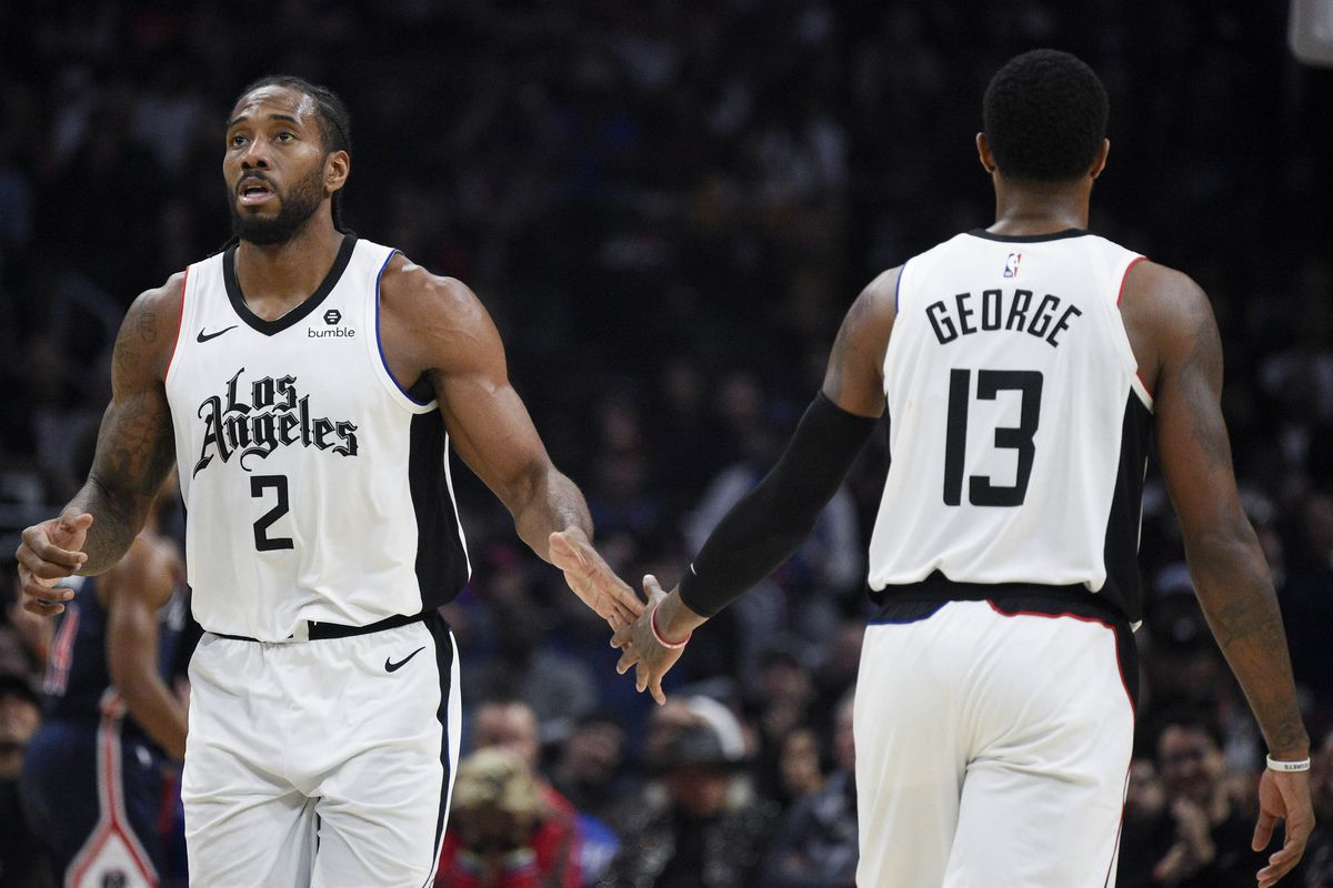 LA Clippers forward Kawhi Leonard shakes hands with forward Paul George during the fourth quarter against Washington Wizards at Staples Center.
