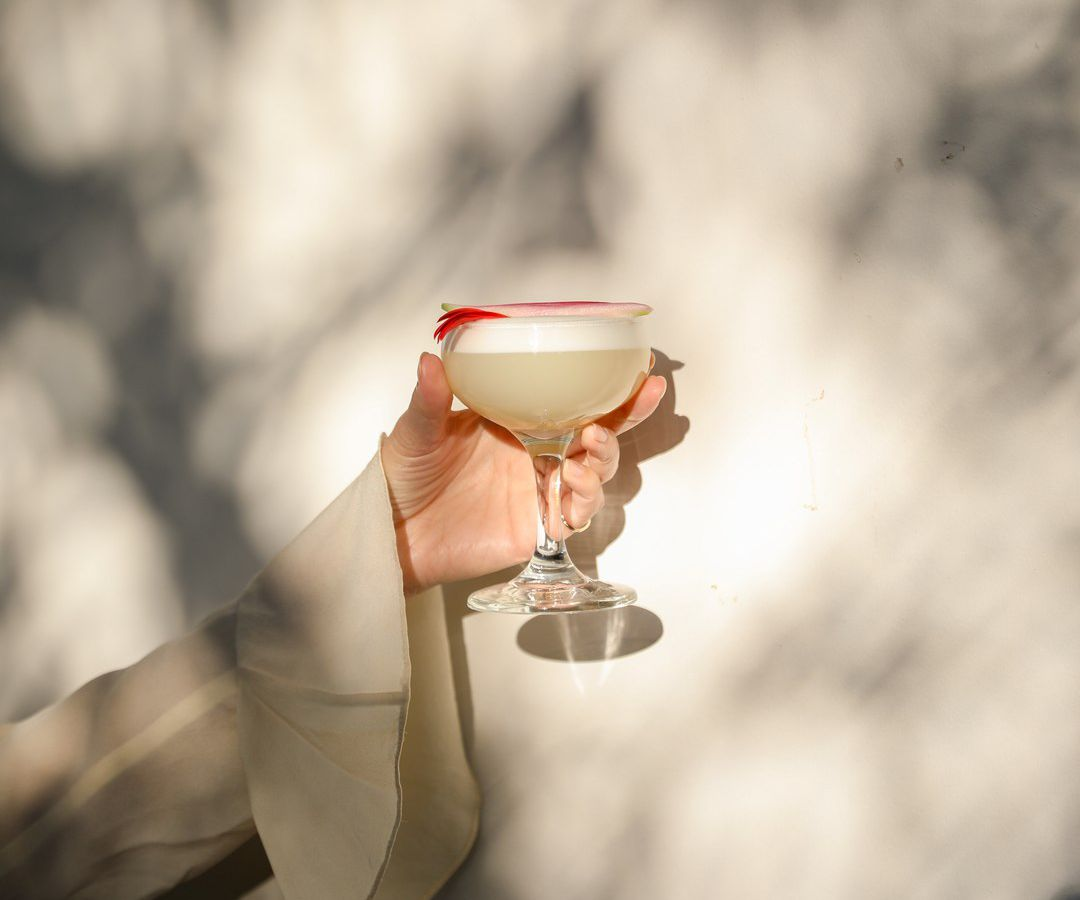 A hand with a flowy sleeve holding a cocktail in the light