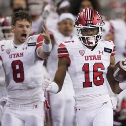 Utah safety Zemaiah Vaughn (16) runs 73 yards as quarterback Jake Bentley (8) reacts on the sideline after Vaughn intercepted a Washington pass during the first half of an NCAA college football game Saturday, Nov. 28, 2020, in Seattle.