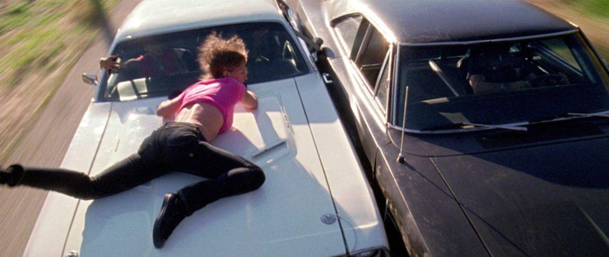 Zoë Bell hangs onto the hood of a speeding car.