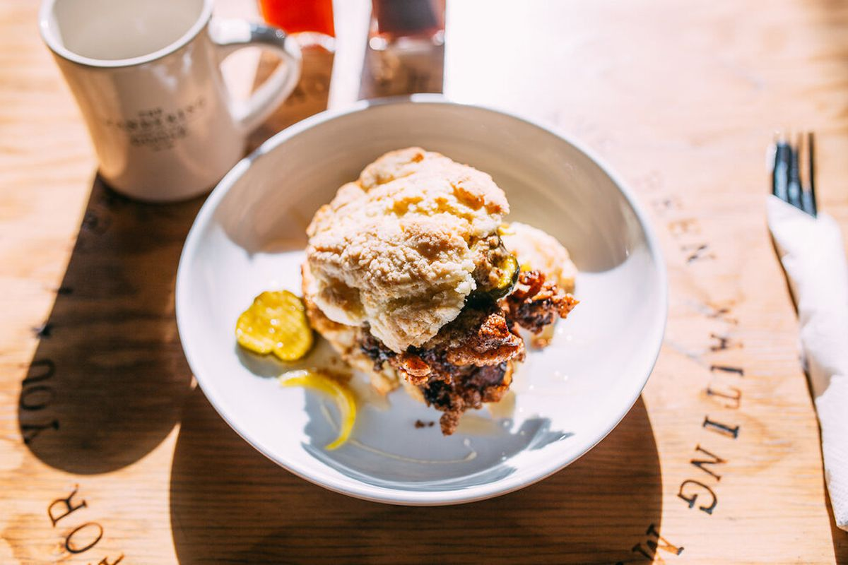 A closeup of a breakfast biscuit sandwich on a wooden table, bathed in sunlight, next to a coffee mug