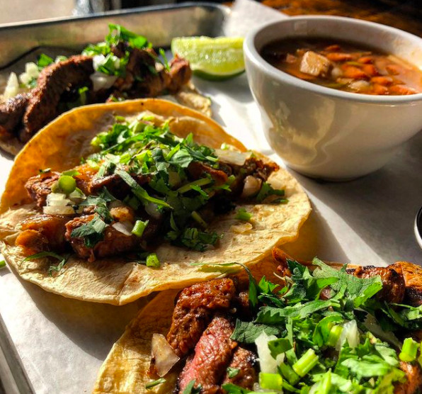 Three steak tacos with a side of red beans in a white ceramic bowl sit atop a square metal tray from Antiguo Lobo in Chamblee, GA