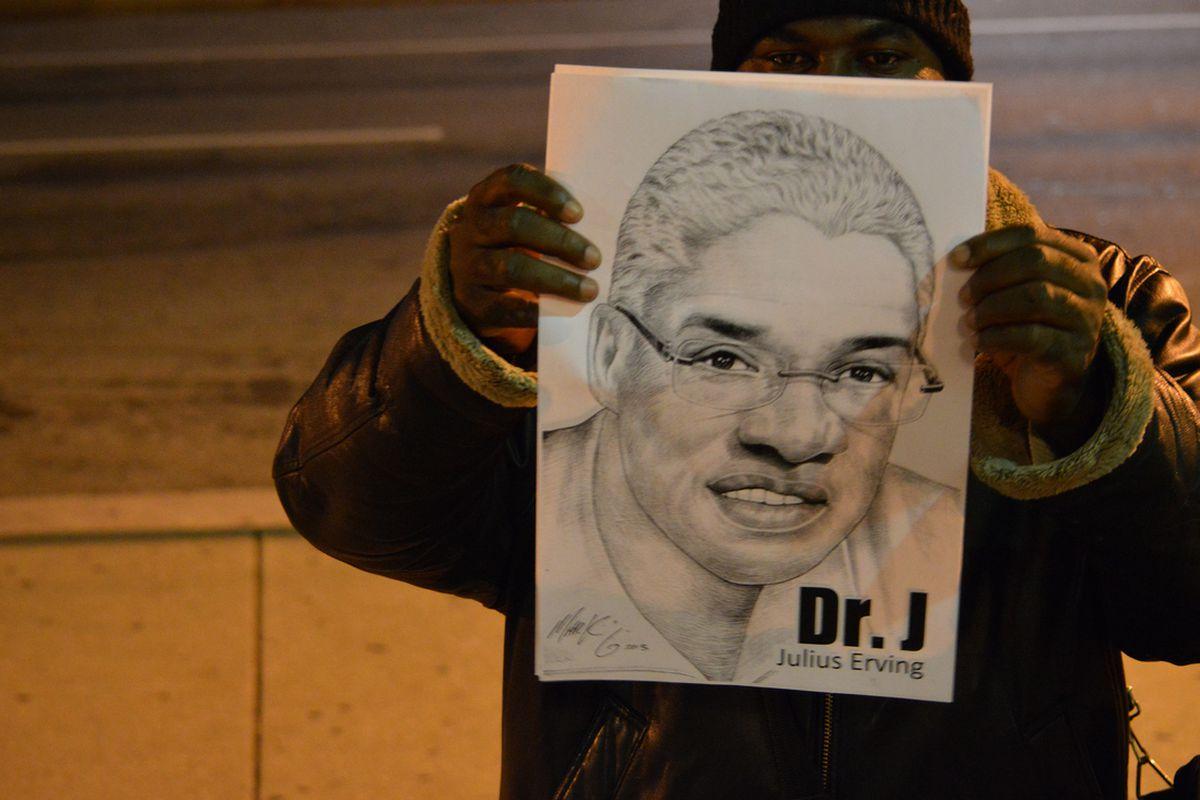 "A fan shows off a pencil drawing of Julius ""Dr. J"" Erving."