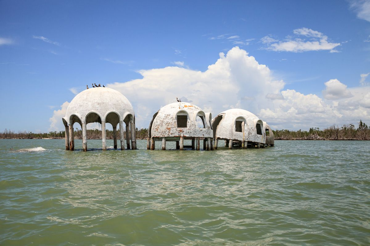A series of dome houses is slowly submerging into the water. There are three domes in varying heights over green-blue water.