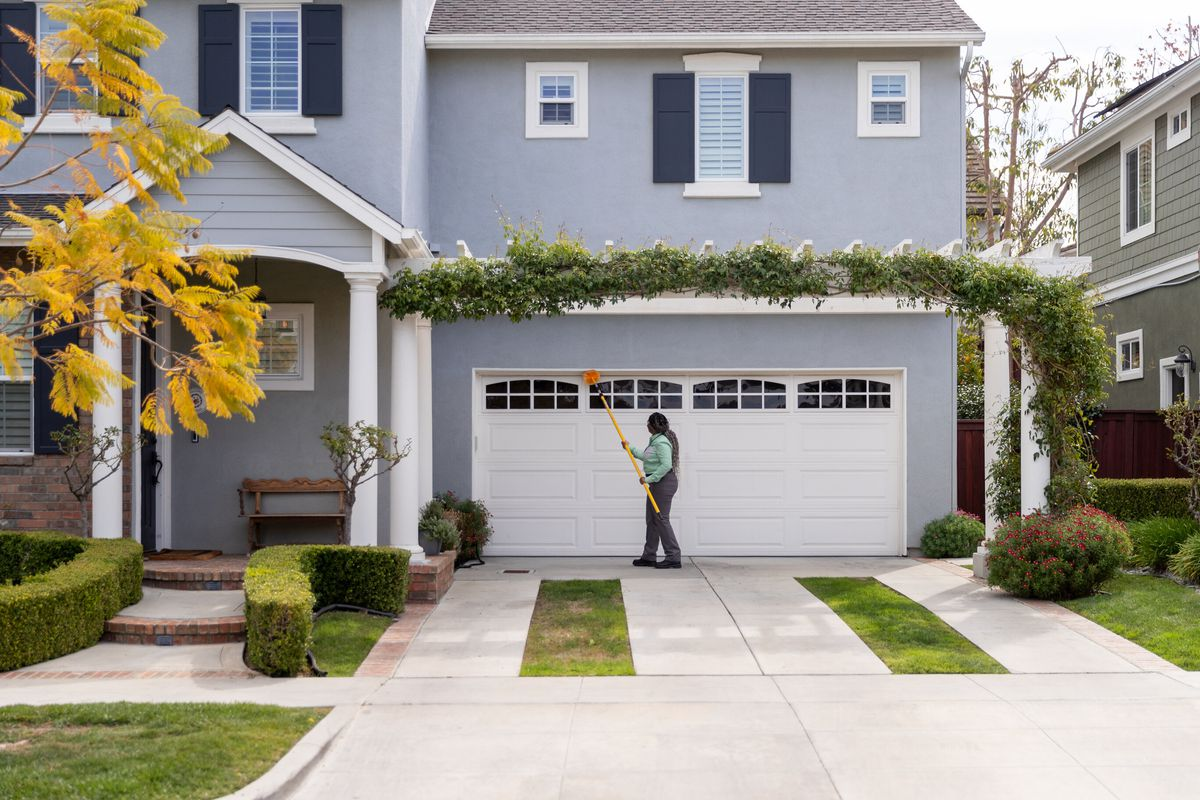 A pest control specialist in a green shirt uses a yellow pest duster on a white garage door of a blue house with black shutters and green lawn.