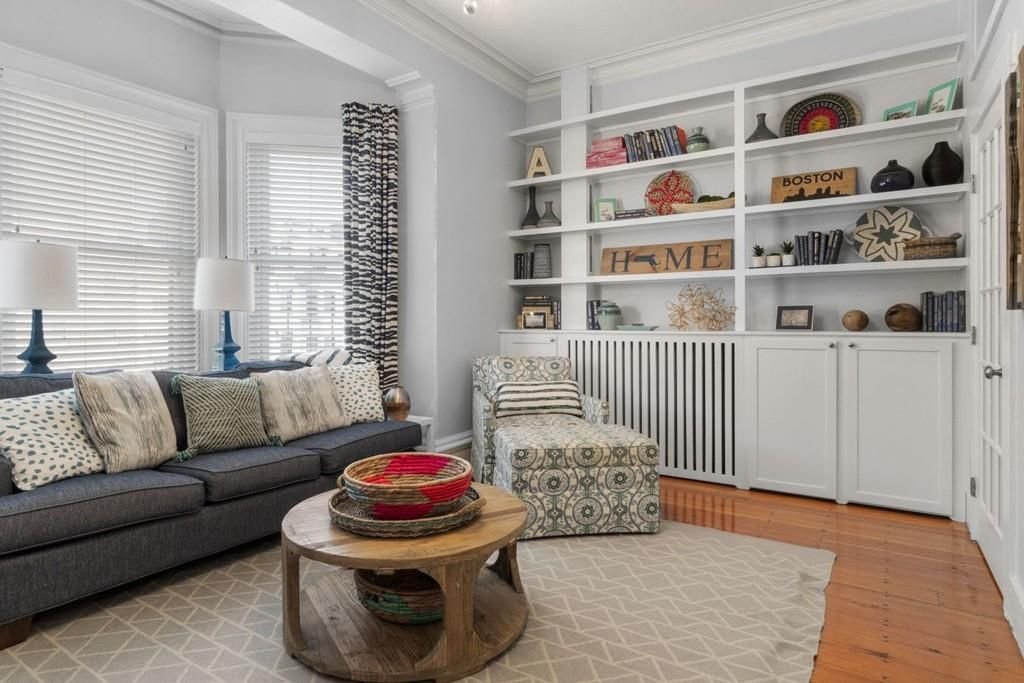 A small living room with built-in shelves, furniture, and a bay window.