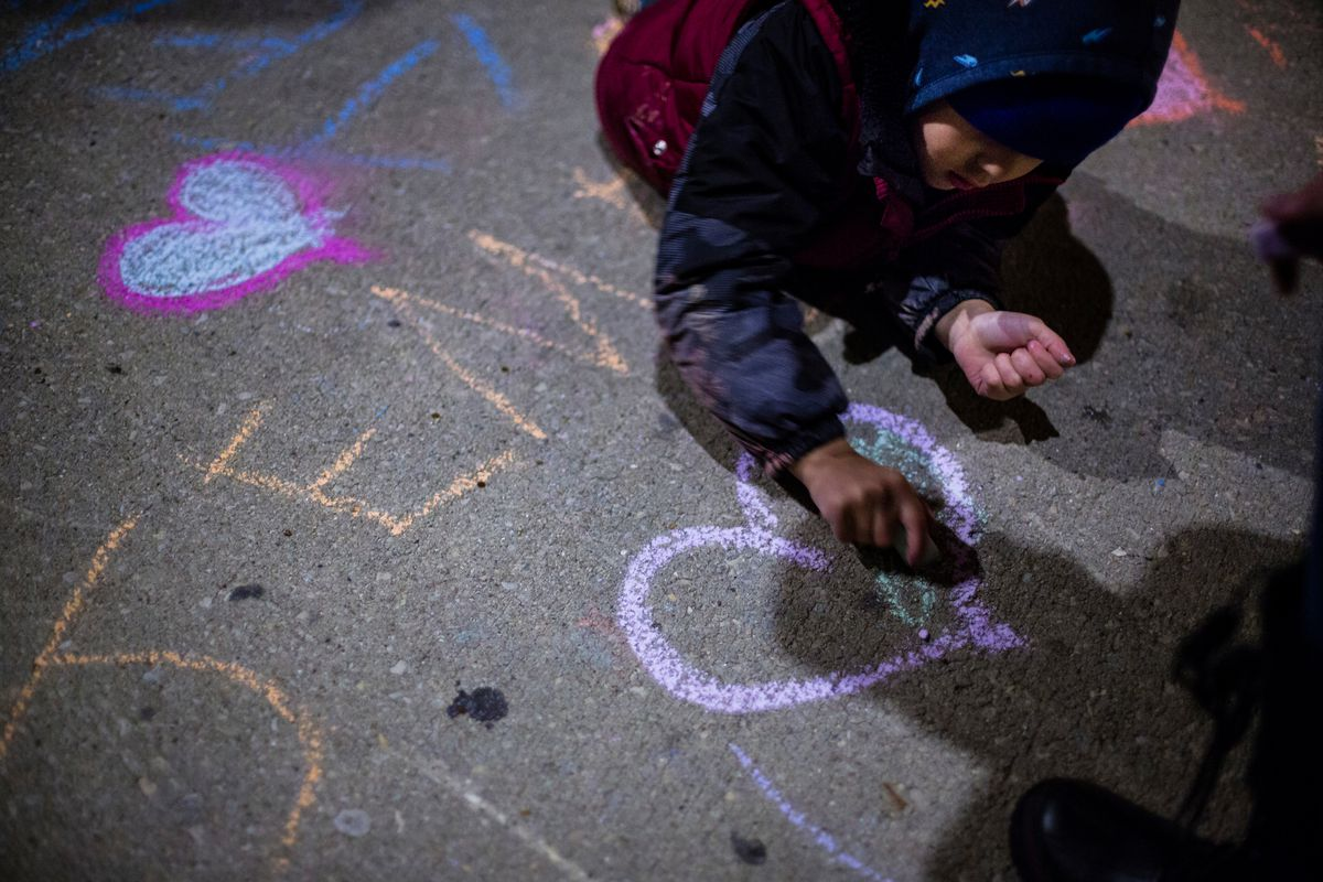 A child writes in chalk on the sidewalk at a vigil for Jemel Roberson at Lane Tech High School, Friday, Nov. 16, 2018.   James Foster/For the Sun-Times