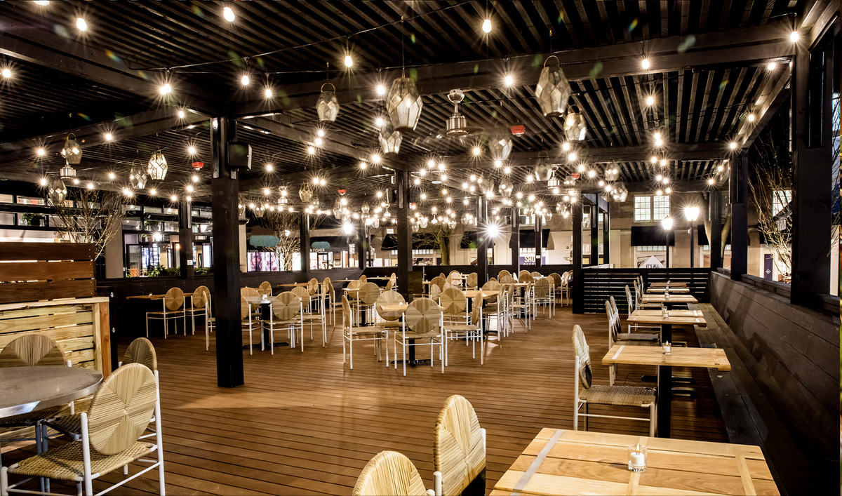 A big restaurant interior with blonde tables and chairs and twinkle lights hanging above