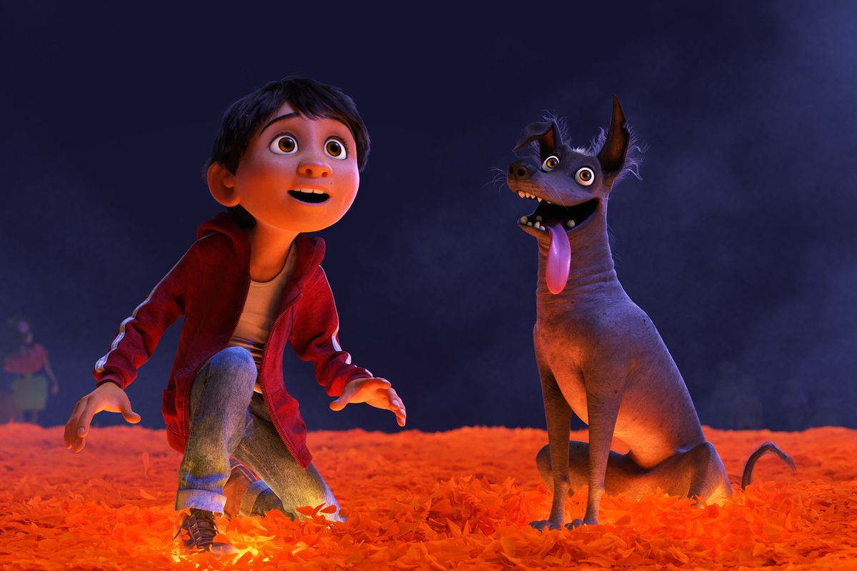 in a scene from the CG-animated movie Coco, a young boy and his dog sit on a bed of glowing orange leaves