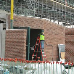 Contractor working on the access gate, along the first-base line wall, in the right-field corner -