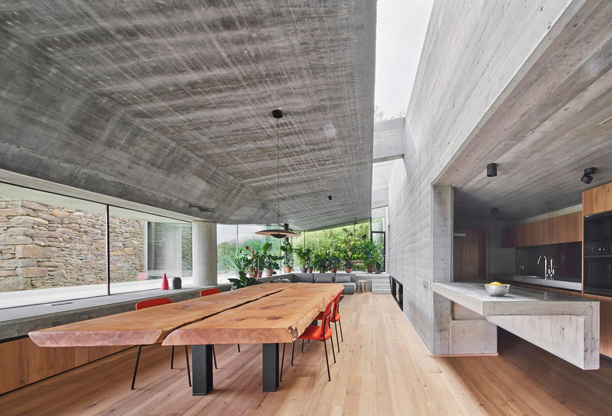 Modern kitchen with wooden dining table and concrete walls.