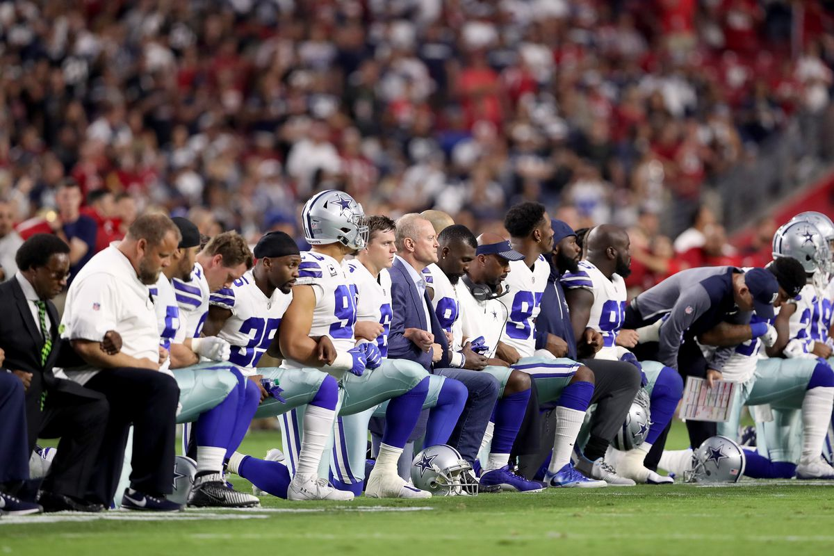 Members of the Dallas Cowboys kneel during the National Anthem on September 25, 2017, before playing the Arizona Cardinals.