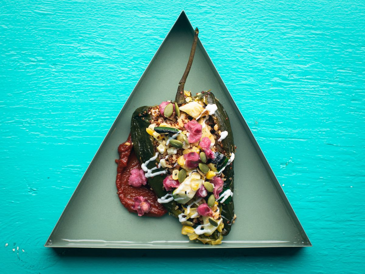 A blue background and on it a triangular plate with a stuffed chile on it with various sauces and ingredients