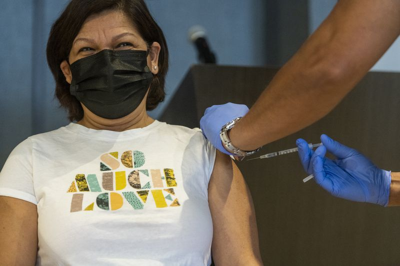 Yolanda Delgado receives her first dose of the Pfizer COVID-19 vaccine last week at a site near Wrigley Field. About 3.2 million Illinois residents have been fully vaccinated.