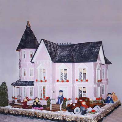 Gingerbread museum with snow on the rooftop and people outside.