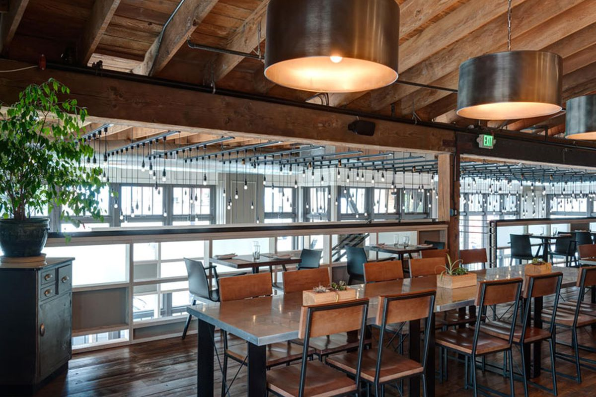 The interior of Lark, with wood tables and large circular hanging lamps.