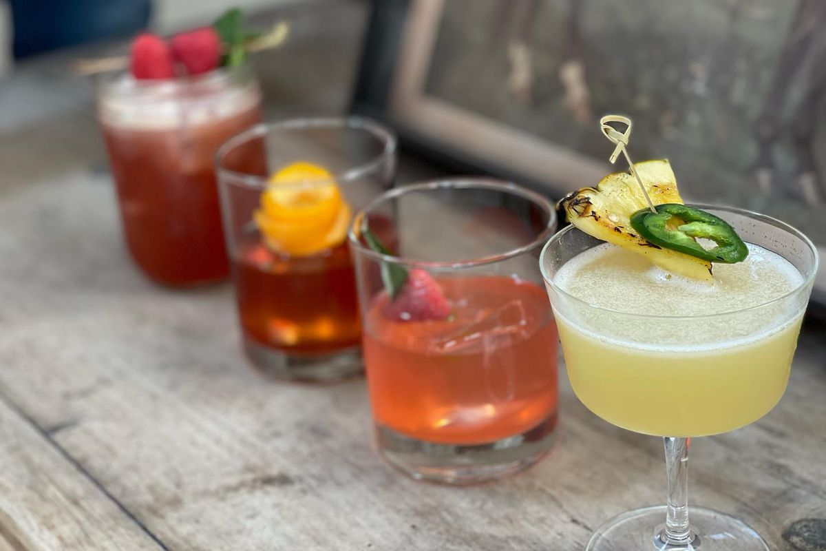 a row of four colorful cocktails