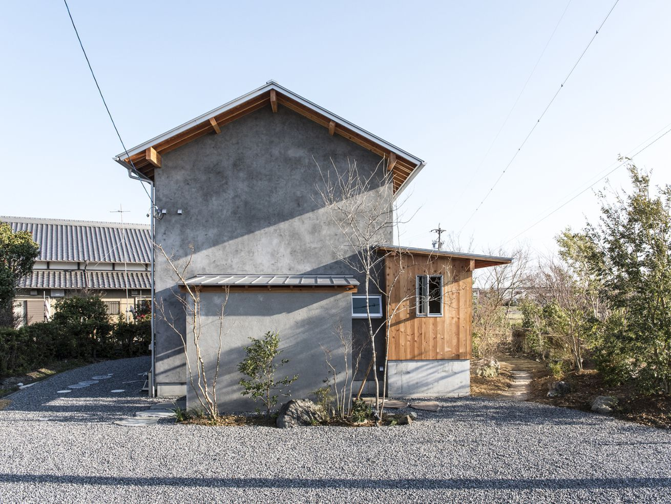 A pitch-roofed house clad in concrete and wood.