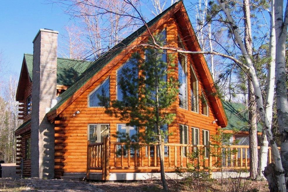 A large wooden cabin with tall windows and an A frame roof with a chimney. There is a porch in front of the cabin.
