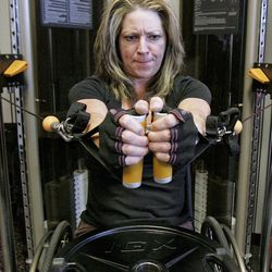 ADVANCE FOR USE SUNDAY, APRIL 22 AND THEREAFTER - In this photo taken April 9, 2012, Cindi Johnson does chest presses during workouts at Premier Fitness in Rockford, Ill.  Johnson was diagnosed in 2005 with multiple sclerosis, myelopathy and a degenerative disc disease. Because of her limited mobility, she uses a wheelchair. She is preparing to compete in the NPC Grand Prix Natural, Bodybuilding, Figure, Physique, Bikini & Wheelchair Championships to be held in Rockford in May.