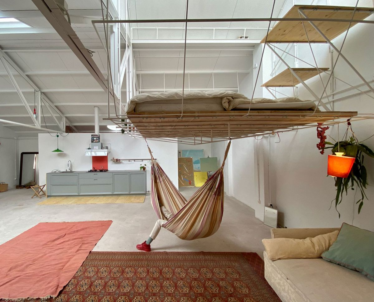 A person hangs in a hammock under an elevated bed platform.