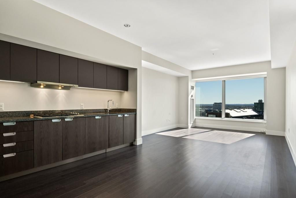 A long, airy, empty living room ending in large windows overlooking a city.