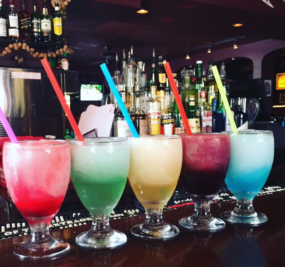 row of colorful frozen cocktails on a bar