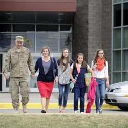 Air Force Tech Sgt. Edward Goettig leaves Fox Hollow Elementary School with his wife, Tracie, and four daughters Bailee, left, Olivia, Sydney and Addie after surprising each one of his daughters at their schools on Thursday, March 6, 2014. Goettig had been deployed to Afghanistan since Aug. 27, 2013.