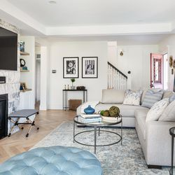 The expansive living room was created by removing partition walls and inserting load-carrying steel beams to support the upper-floor spans. The gas fireplace and large TV screen create a focal point for the room. <em>Painting contractor, interior: </em><a class=