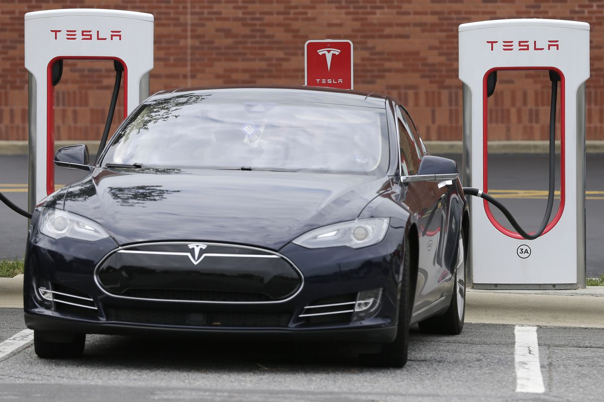 FILE- In this June 24, 2017, file photo, a Telsa Model 3 car recharges at a Tesla charging station at Cochran Commons shopping center in Charlotte, N.C.