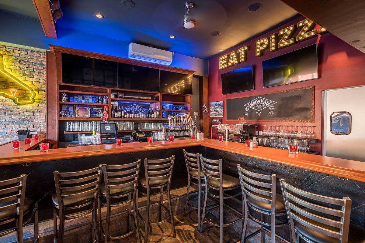 A corner bar with a neon sign advertising pizza.