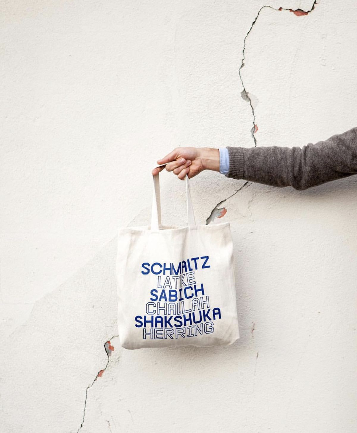 A hand in a tweed jacket holds out a tote with a list of words written in light and dark blue fonts