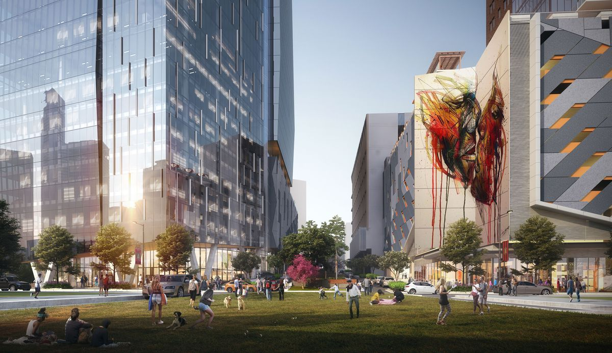 A sprawling lawn is filled with people, below the glassy office tower and art-decorated apartment component.