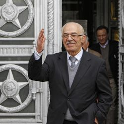 Syrian opposition member Hassan Abdul-Azim waves to press as he walks out  of the Russian Foreign Ministry in Moscow, Russia, Monday, April 16, 2012 after talks.