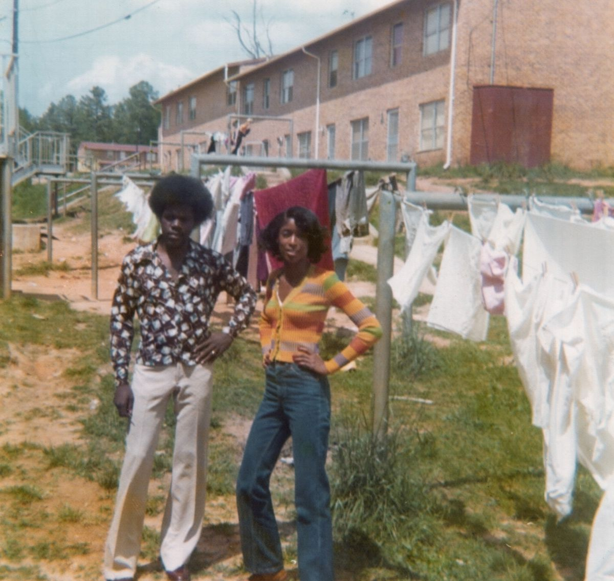 A couple standing next to hanging laundry in Atlanta.
