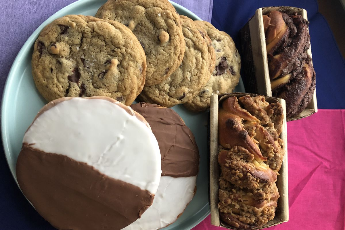 Chocolate chip cookies, black-and-whites, and babkas sit on a purple table from Small Good Bakery