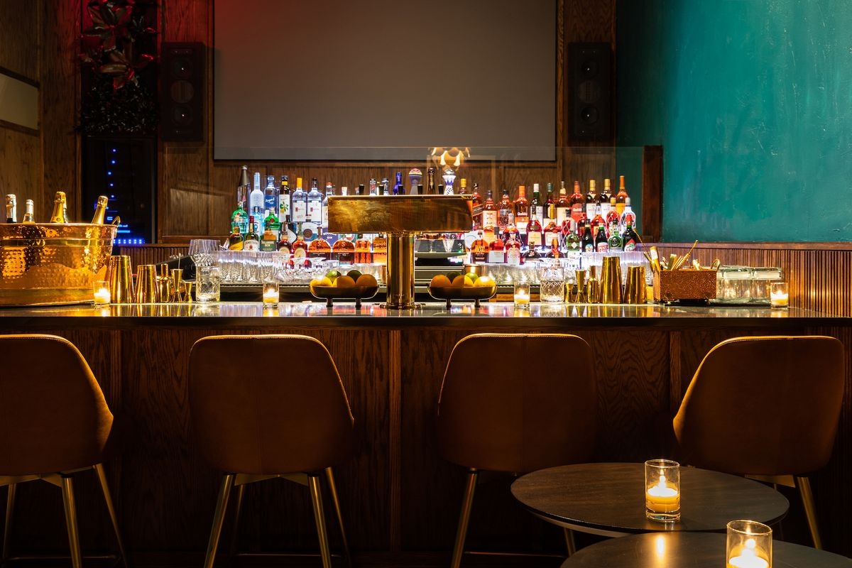 A bar with several alcohol bottles in the back, and a brass lamp on the counter in the front.
