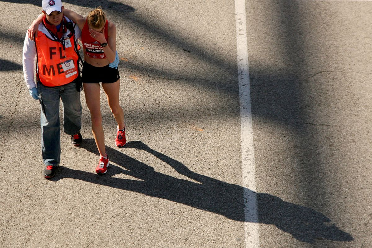 HOUSTON, TX - JANUARY 14: A runner is assisted as she holds her head after finishing in the U.S. Marathon Olympic Trials January 14, 2012 in Houston, Texas. (Photo by Thomas B. Shea/Getty Images)