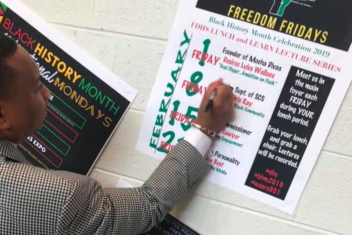 "Interim superintendent Joris Ray scratches out ""interim"" on a flier at Douglass High School in February."