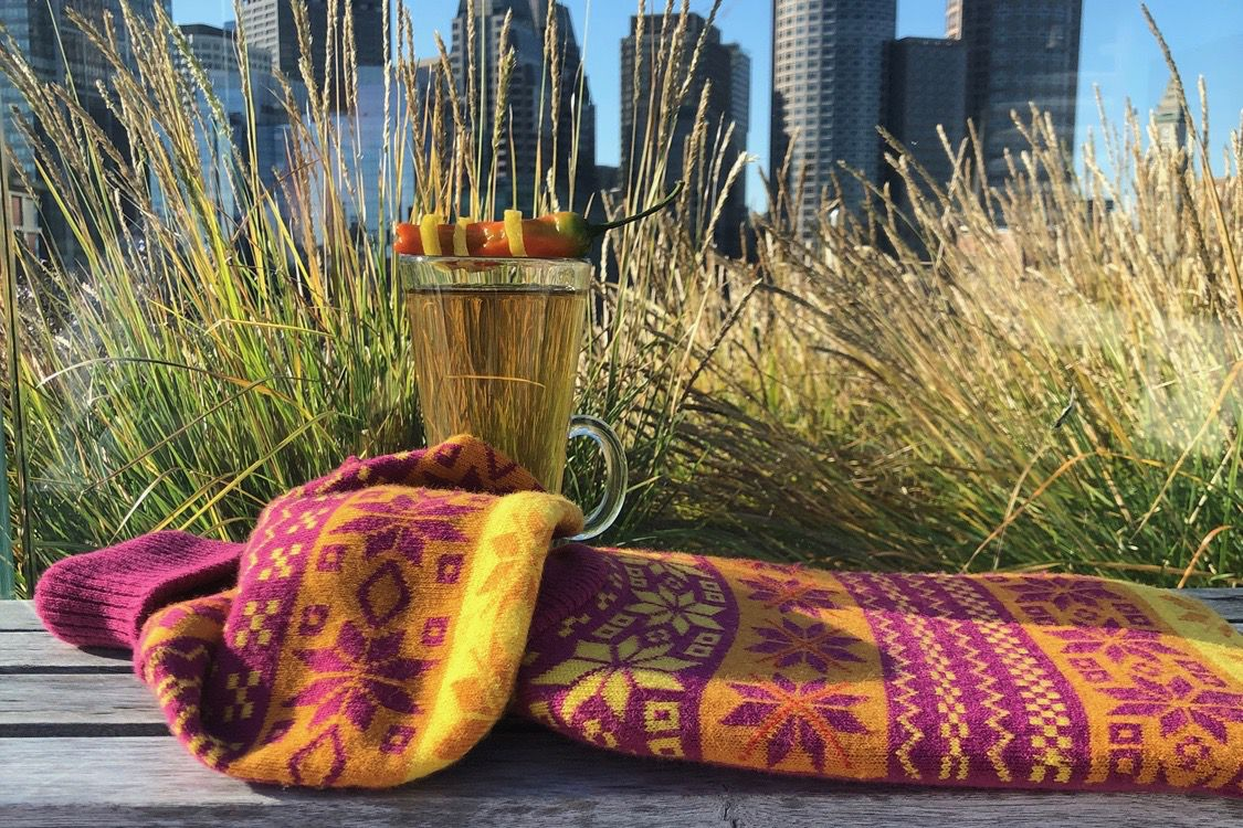 A hot toddy in a tall clear glass sits on a patterned scarf on a bench at a rooftop bar