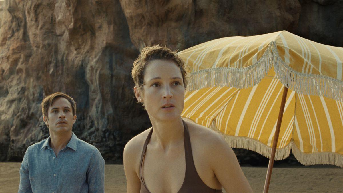 Gael García Bernaland Vicky Krieps on the beach, with a yellow umbrella behind them.