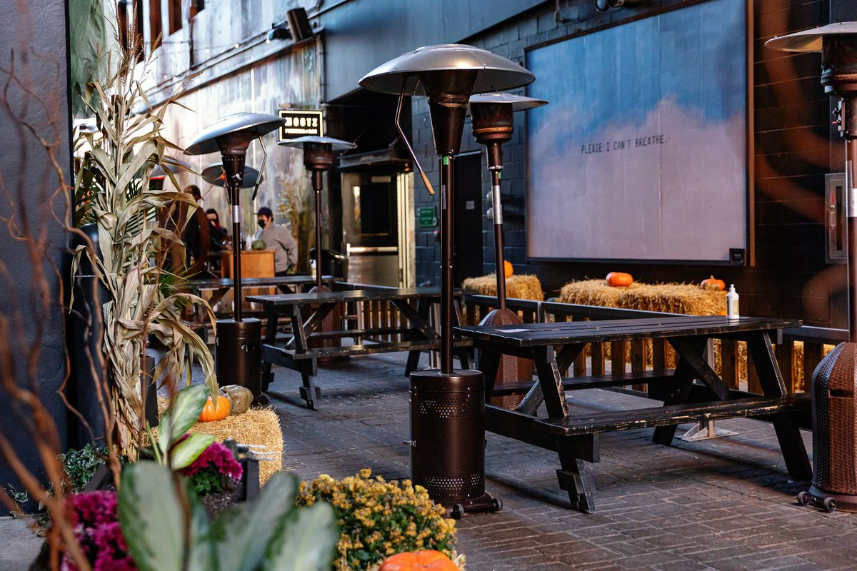 Picnic tables and heaters are surrounded by autumn decor at the Skip in the Belt Alley.
