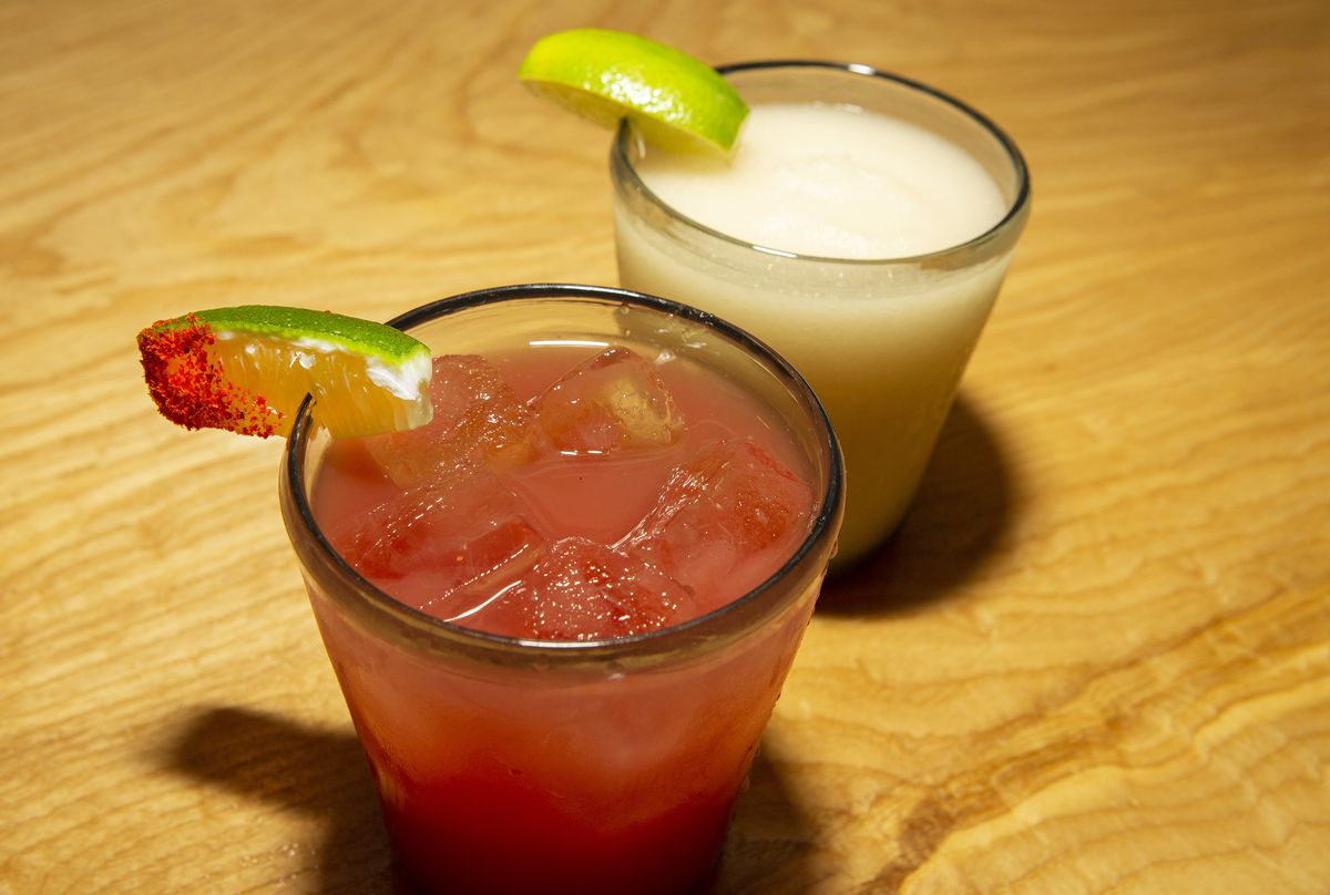 Two small glasses of agua fresca, one pink and one white