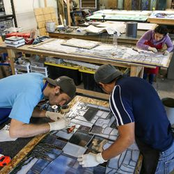 """Preston Powell, front left, Venustiano Gregorio, front right, and Zabdi Zetina, back right, work on """"The Roots of Knowledge,"""" a 200-foot-long stained glass installation for Utah Valley University, at Holdman Studios in Lehi on Friday, Nov. 4, 2016. A Guardian UK reporter called the work """"one of the most spectacular stained glass windows made in the past century."""""""
