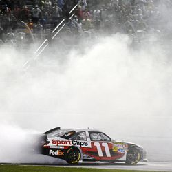 Denny Hamlin celebrates with a burnout after winning the NASCAR Sprint Cup Series auto race at Atlanta Motor Speedway, Sunday, Sept. 2, 2012, in Hampton, Ga.