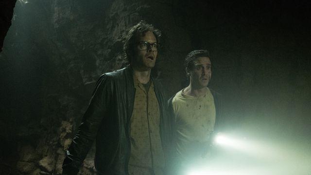 Richie (Hader) and Eddie (Ransone) gaze, terrified, into the darkness.