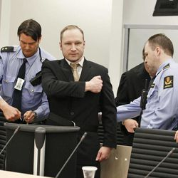 Accused Norwegian Anders Behring Breivik, centre,  gestures as he arrives at the courtroom in Oslo, Norway  Monday, April 16, 2012 . The terror trial against an anti-Muslim fanatic who confessed to killing 77 people in Norway starts amid worries that he will use the proceedings to showcase his radical views. After opening statements, Anders Behring Breivik is set to testify for five days, explaining why he set off a bomb in downtown Oslo, killing eight, and then shot to death 69 people, mostly teenagers, at a Labor Party youth camp on Utoya island, outside the Norwegian capital.