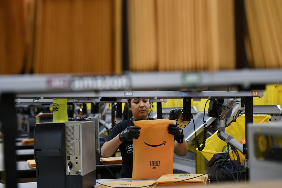 An Amazon warehouse worker packs an envelope in a warehouse.