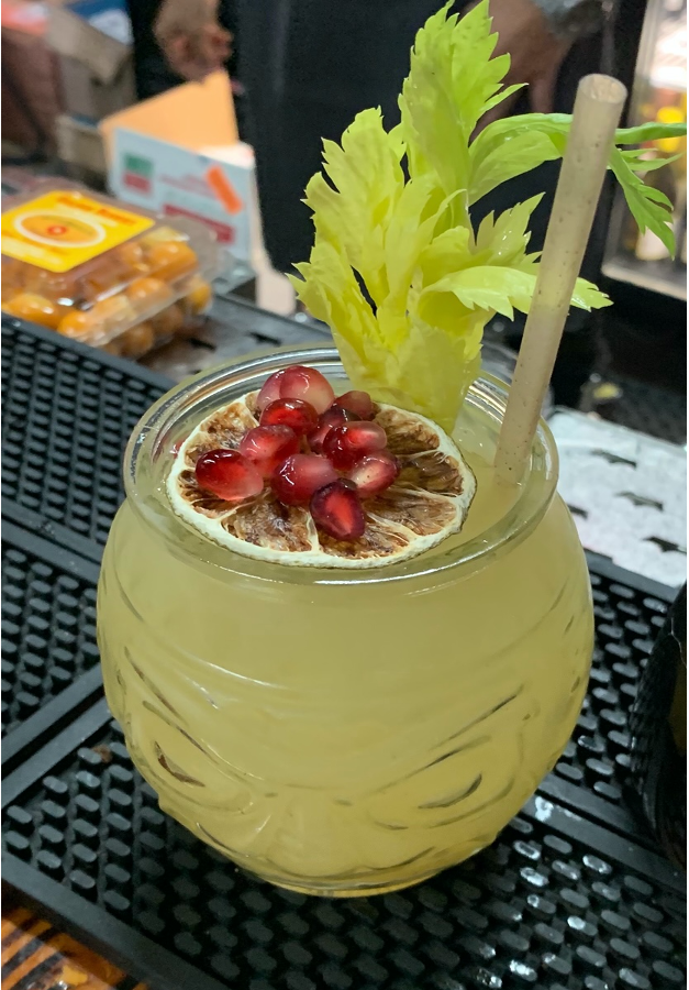 A yellow colored cocktail in a squat glass with a piece of celery, pomegranate seeds and a dried citrus slice